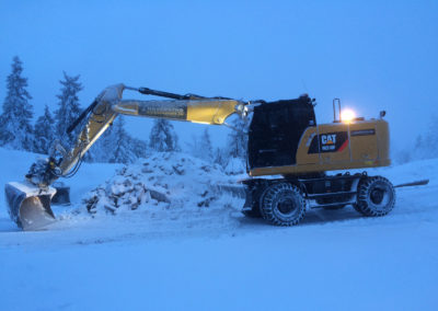 Hjulgraver. Cat M318F. Graving av tomt på vinterstid.